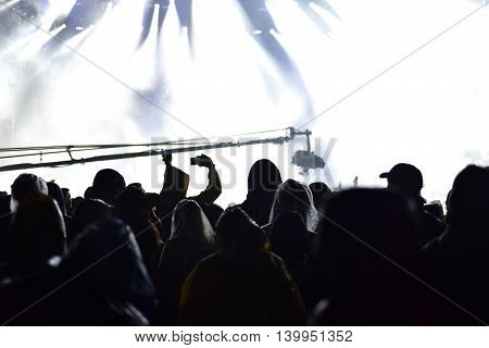 Crowd at a live concert. Stage lights in the background