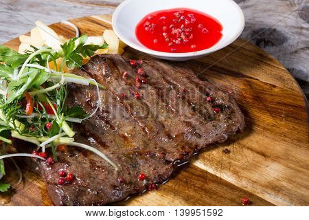 Fried beef steak served with cranberry sauce and french fries