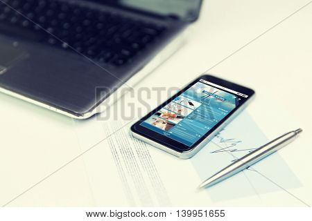 business, technology and mass media concept - close up of smartphone with business news page on screen, laptop computer and pen on office table