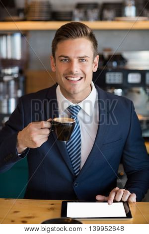 Portrait of businessman using digital tablet while having coffee in café
