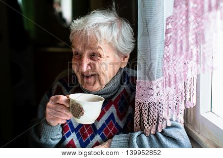Happy elderly woman portrait sitting at the table and drink tea.