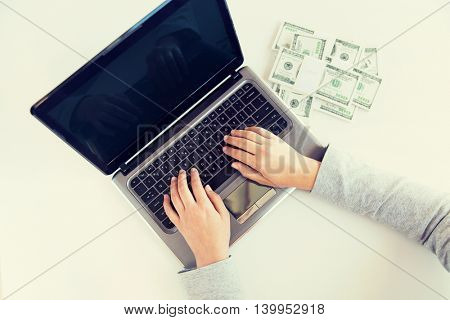 business, finance, saving, technology and people concept - close up of woman hands with laptop computer and us dollar money