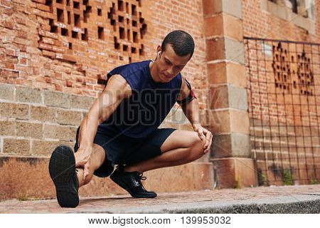 Concentrated male athlete stretching legs after jogging