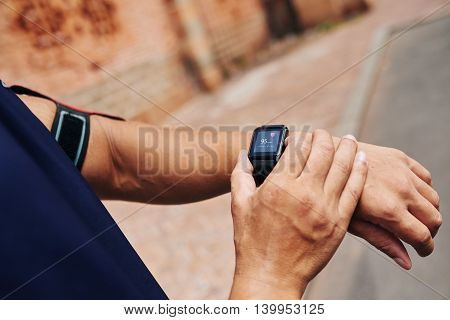 Cloe-up image of sportsman checking his pulse on smart watch