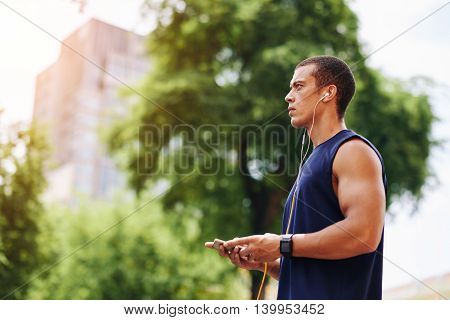 Fit man with smartphone ready for morning training