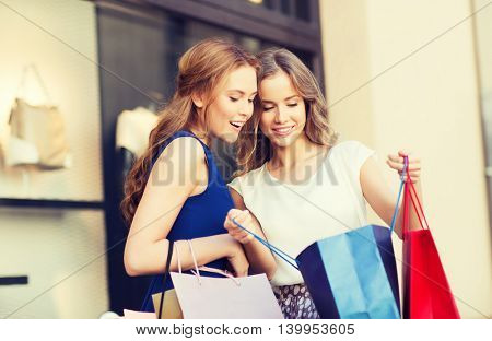 sale, consumerism and people concept - happy young women looking into shopping bags at shop window in city