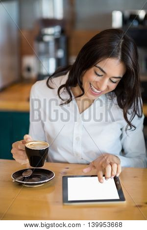 Close-up of businesswoman using digital tablet while having coffee in café