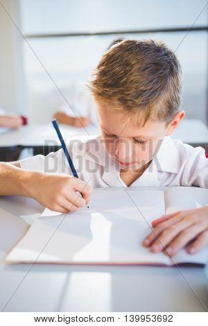 Schoolboy doing homework in classroom at school