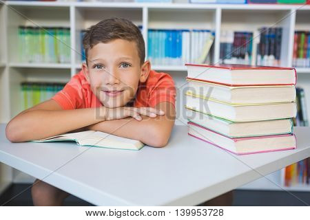 Portrait of smiling schoolboy leaning on a book in library at school