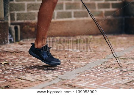 Legs of sportsman exercising with skipping rope
