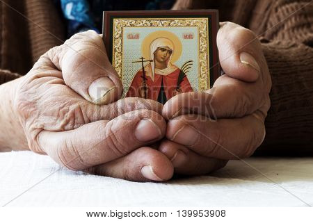 very old senior woman hands wrinkled skin  with orthodox icon
