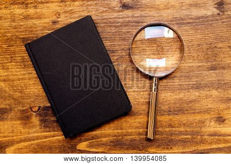 Loupe magnifying glass and notebook on wooden desk top view concept of searching and investigating