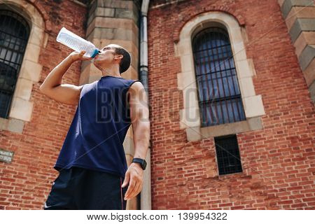 Male athlete enjoying sip of fresh water