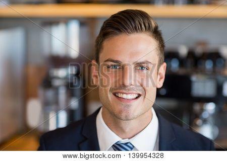 Portrait of smart businessman in café