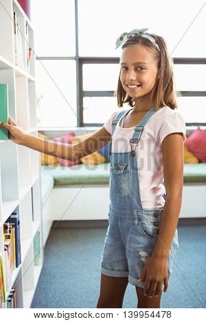 Portrait of girl taking a book from bookshelf in library at school