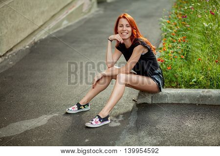 Young beautiful woman sits on rock border