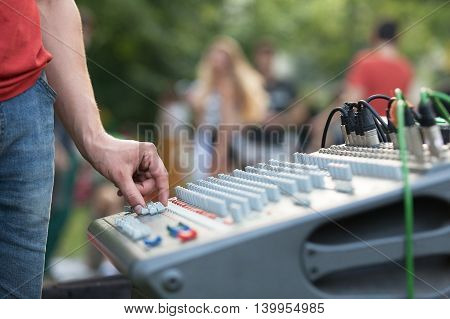 Sound adjustment. Hand over an audio mixing console.