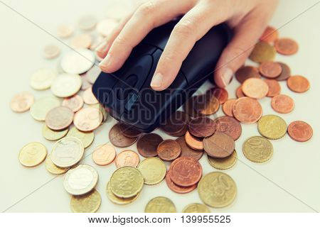 business, finance, money, internet earning and people concept - close up of hand with computer mouse on euro coins