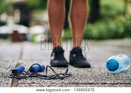 Skipping rope and water bottle on the ground near feet of sportsman