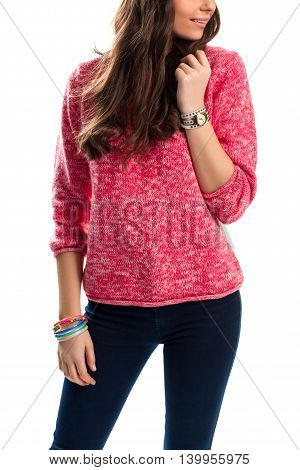 Lady in pink sweater. Watch and bracelets on hands. Model wears dark stretch pants. Stylish woolen pullover.