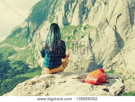 Female traveler in the mountains Опи: Traveler young woman sitting on rock stone in summer mountains rear view. Image with instagram color