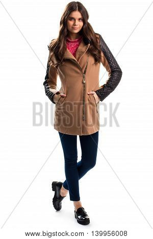 Girl in beige coat. Dark navy pants and shoes. Trendy coat with quilted sleeves. Garment of fleece and leather.