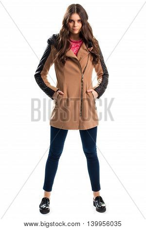 Lady in short beige coat. Navy pants and black shoes. Fashionable coat with leather inserts. Model posing on white background.