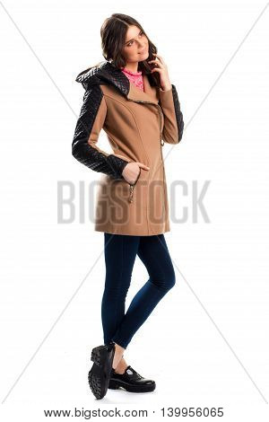 Girl in beige coat smiling. Black shoes on platform. New wear for spring. Outfit with warm fleece coat.