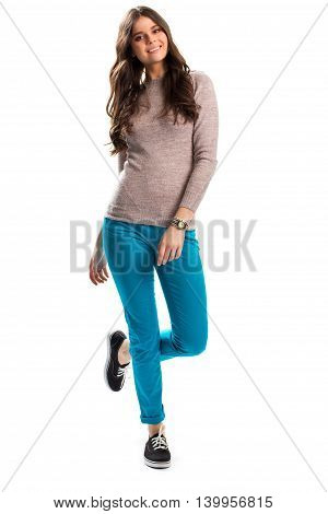 Woman in beige pullover smiles. Black sneakers and turquoise pants. Comfortable everyday apparel. Outfit on white background.