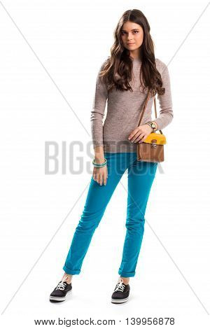 Young lady in beige pullover. Black shoes and turquoise pants. Trendy canvas sneakers. Model with leather bag.