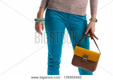 Lady's hand holds a bag. Striped bracelet and colorful pants. Leather handbag and wrist accessories. Merchandise at low price.