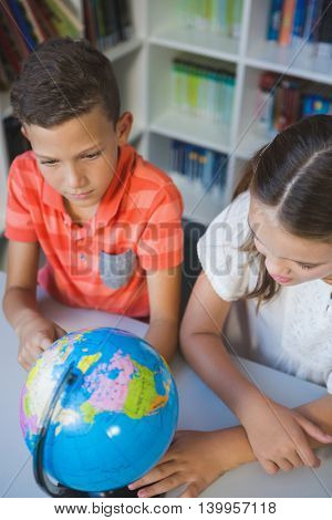 School kids studying globe in library at school