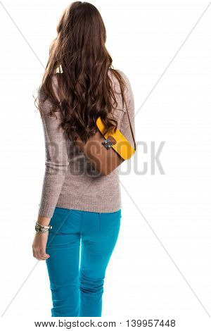 Woman with a bag. Back view of beige sweatshirt. Comfortable clothes for travel. Fashionable spring outfit with purse.