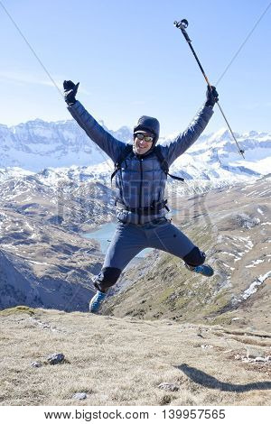 happy hiker jumping in the high of the mountain
