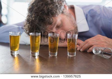 Drunken man sleeping on a bar counter at restaurant