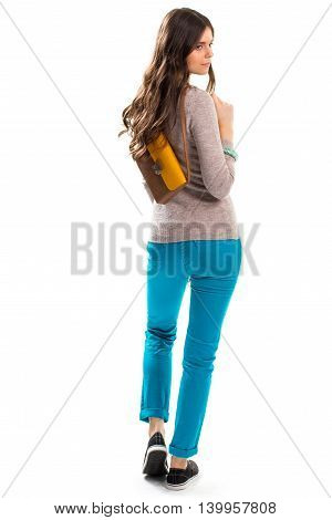 Girl with bag looks back. Black sneakers and beige sweater. Model in trendy pants. Casual garments and accessories.