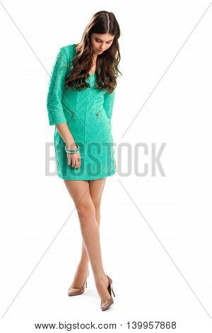 Woman in dress looks down. Turquoise dress and beige heels. Date outfit with glossy shoes. New collection of elegant clothing.