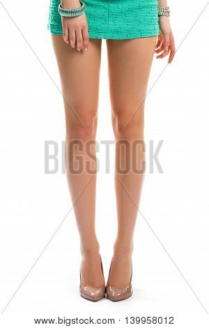 Girl's legs in beige heels. Short dress and footwear. Luxury shoes for evening outfit. Thin legs of model.