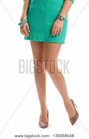 Woman's legs in beige heels. Short turquoise dress and watch. Beautiful apparel and accessories. Be charming this summer.