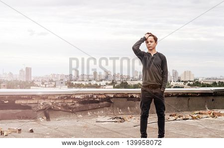 teenager stands on the roof of a tall building in the city center
