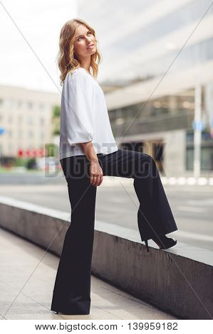 Outdoors portrait of business woman in full-length put her foot on curb. Split toned photo