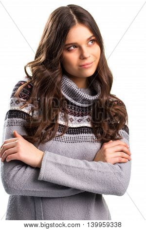 Woman in pullover slightly smiling. Young lady with crossed arms. Think of the better case. Keep calm and gather thoughts.