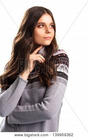 Thoughtful girl on white background. Colorful pattern on pullover. Thoughts and hopes. Make a wise choice.