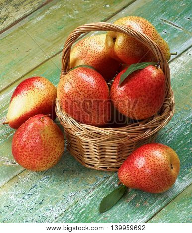Arrangement of Ripe Yellow and Red Pears with Leafs in Wicker Basket closeup on Cracked Wooden background