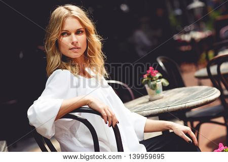 Beautiful young blond lady sitting at table in outdoor cafe on sunny warm day. Split toned photo
