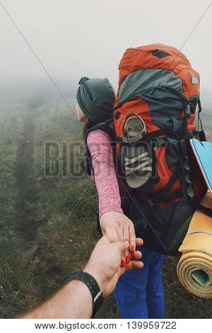 Brave woman guiding traveler into the fog in the mountains. Follow me. Woman holding man by hand and going in mountains.