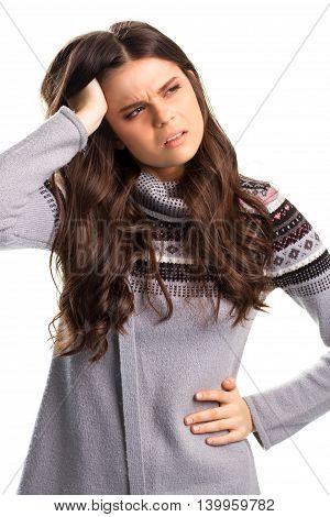 Girl holds head with hand. Lady in gray sweatshirt. Feeling sick and tired. Hard to handle stress.