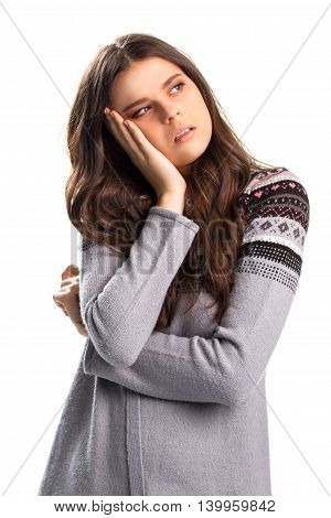 Woman holds head with hand. Young lady in casual sweater. I've heard it all before. Can't stand the boredom.