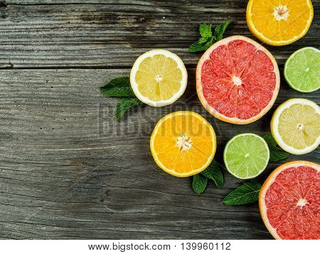 Photo of a sliced grapefruit orange lemon and lime on a old rustic slab of barn board.