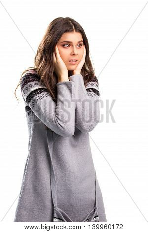 Woman holds face with hands. Scared lady in gray sweater. The news is shocking. This can't be true.